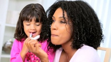 Loving African American mother with cute young daughter watching mom putting on lipstick