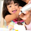 Little Ethnic Girl Young Mom Icing Cupcakes - Stock Photo