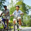 Young Ethnic Family Cycling Together - Stock Photo