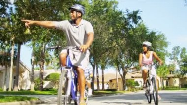 Young ethnic family cycling together suburban roads in sunshine