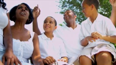 Young African American parents spending time with their children outdoors on park bench shot on RED EPIC — ストックビデオ #18777123