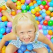 Laughing Little Girl Playing Plastic Balls - Stock Photo