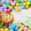 Stock Video: Laughing Little Girl Playing Plastic Balls