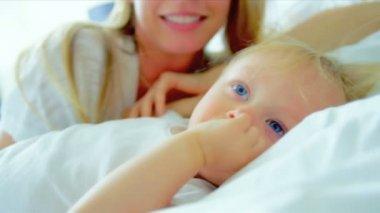 Jeune mère enfant jouant sur lit — Vidéo