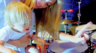 Cute blonde baby girl supported by young mom while playing with drumsticks and drums home studio shot on RED EPIC