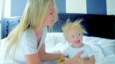 Young Caucasian mother bouncing her cute baby on bed shot on RED EPIC