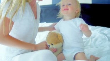 Cute blonde baby boy holding teddy bear playing with beautiful young mother at home shot on RED EPIC