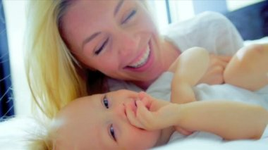 Beautiful young mother tenderly playing with her baby daughter at home shot on RED EPIC