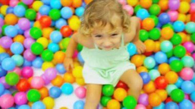 Cute blonde toddler sitting in multi coloured plastic balls in big paddling pool shot on RED EPIC