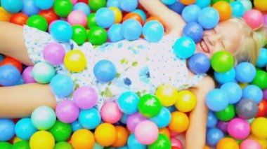 Pretty young Caucasian girl having fun playing in multi coloured ball pool shot on RED EPIC