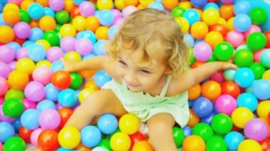 Smiling little Caucasian girl playing in pool full colorful plastic balls shot on RED EPIC