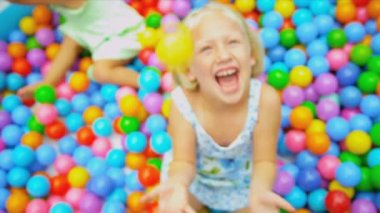 Cute blonde girl laughing in big paddling pool filled with multi coloured plastic balls shot on RED EPIC