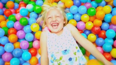 Smiling little Caucasian girl laughing in pool full colorful balls shot on RED EPIC