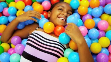 Laughing young ethnic girl playing in plastic pool full colorful balls shot on RED EPIC