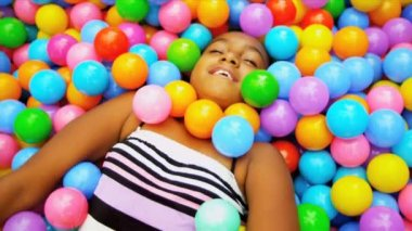 Pretty young ethnic girl having fun playing in multi colored ball pool shot on RED EPIC