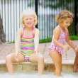 Laughing Little Girls Enjoying Swimming Pool - Stock Photo