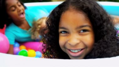 Close up smiling little African American girl having fun with friends paddling pool full colored plastic balls