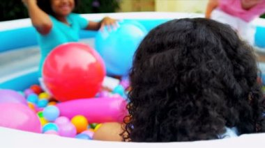 Pretty young ethnic girl in forefront having fun playing with friends in multi coloured ball pool shot on RED EPIC