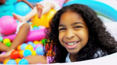Laughing multi ethnic little girls playing in ball pool together shot on RED EPIC