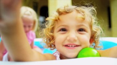 Smiling pre school Caucasian girl in forefront having fun playing with sister ethnic friends in multi coloured ball pool shot on RED EPIC