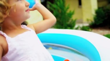 Full frame close up cute pre school girl playing colored plastic balls friends garden pool