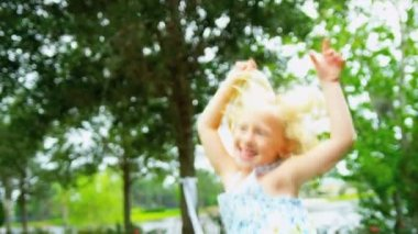 Cute little blonde girl jumping for joy in sunshine in home garden