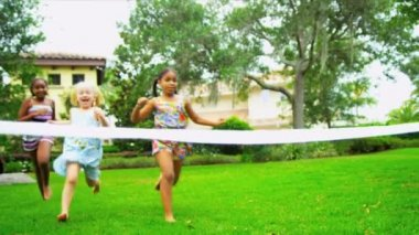 Cute young multi ethnic girls having fun running race in practice sport competition home garden shot on RED EPIC
