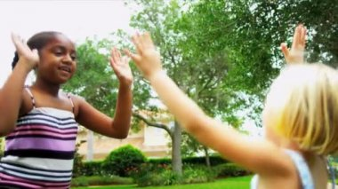 Young Caucasian African American friends celebrating achievement giving high five