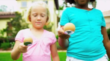 Little African American Caucasian girls enjoying sports day egg and spoon race in garden shot on RED EPIC
