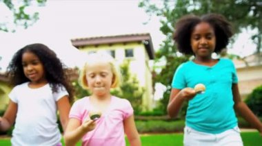 Little ethnic girls enjoying fun sports day egg and spoon race in garden shot on RED EPIC