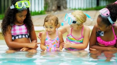 Laughing little Caucasian and African American girls with masks snorkels playing outdoors in swimming pool shot on RED EPIC