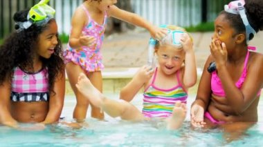 Laughing little multi ethnic girls with masks snorkels playing outdoors in swimming pool shot on RED EPIC