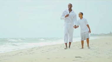 Loving ethnic father walking and laughing with son on beach shot on RED EPIC