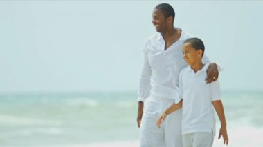 Ethnic parent spending holiday walking with son on beach shot — Stock Video