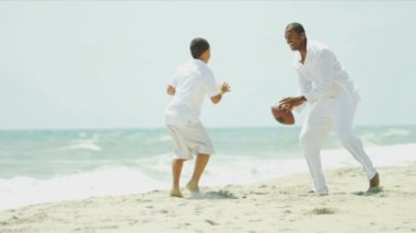 American football game of diverse parent and son on beach — Stock Video