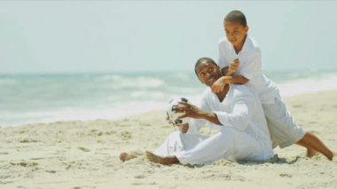 Football time of African American son and father on beach — Stock Video