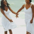 African American parent enjoying time together daughter on beach - Stock Photo