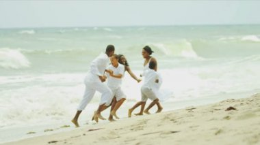 Ethnic family together laughing playing in surfs on beach — Stock Video