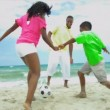 Diverse father playing together sons and daughter football on beach - Stock Photo