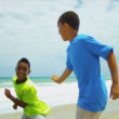 Stock Video: Young AfricAmericbrothers playing together on beach
