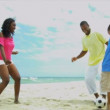 African American children enjoying summer kicking football with father on beach — Stock Video