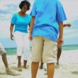 Ethnic parents kicking with soccer ball with sons teenage daughter on beach - Stock Photo