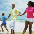 African American parents children holding hands enjoying running in ocean surfs - Stock Photo