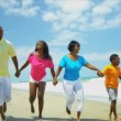 African American family have fun together on beach holding hands - Stock Photo