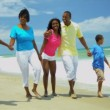 African American family enjoying summer vacation walking together on beach - Stock Photo