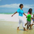 African American parents walking and chilling with children holding hands on beach - Stock Photo