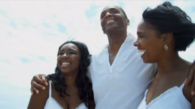 African American family spending together time on beach all dressed in white — Stock Video