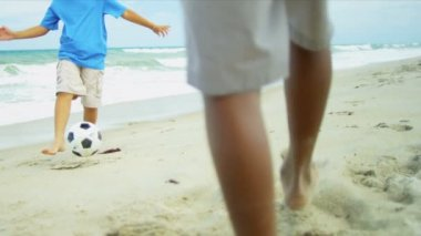 Ethnic brothers kicking together football on beach — Stock Video