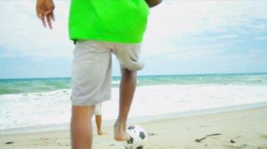 Afryki amerykański chłopcy gry w piłkę nożną na plaży strzał na epicki czerwony — Wideo stockowe