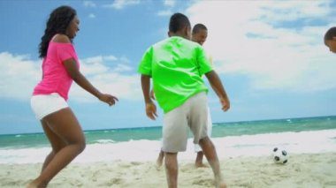 Soccer game of African American father wit his happy children by ocean — Stock Video